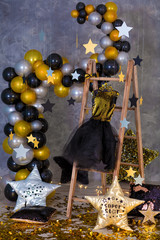 Decoration of golden party dress with leather jacket hanging on wooden hanger in club studio decorations.