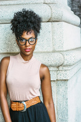 Portrait of Young African American Woman in New York. Young black female college student with afro hairstyle wearing sleeveless light color top, black skirt, eye glasses, standing by column on street