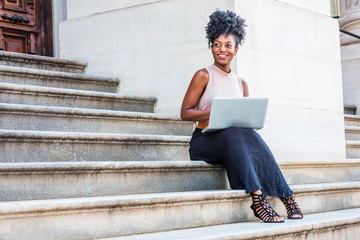 Way to Success. Young African American woman with afro hair, wearing sleeveless top, black skirt, sandals, sitting on stairs outside office building in New York, working on laptop computer, smiling..