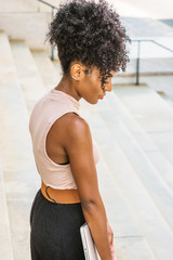 Young African American Girl with afro hairstyle, white ear bead pin, wearing sleeveless light color top, dark orange belt, black skirt, standing on stairs outside on campus in New York, looking down..