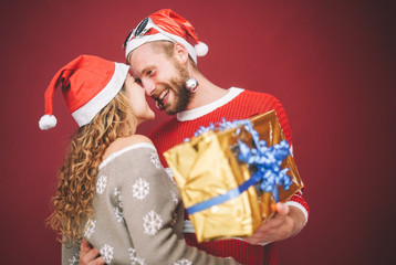 Happy boyfriend surprising his girlfriend giving her a christmas present - Young couple having fun celebrating and kissing in xmas holidays - Love, x-mas event and millennial relationships concept