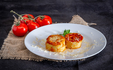 Italian rondelli with pomodoro sauce and cheese on rustic background.