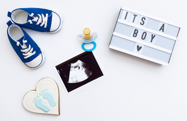 "flatlay pregnancy composition with space for text on white background. top view of children's accessories: toys, pacifier, baby screen, baby projector lamp ""it's a boy"" and delicious gingerbread"