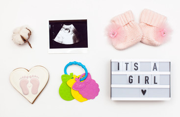 """flatlay pregnancy composition with space for text on white background. top view of children's accessories: toys, pacifier, baby screen, baby projector lamp """"it's a girl"""", a cotton flower"""