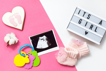 "flatlay pregnancy composition with space for text on white and pink background. top view of children's accessories: toys, pacifier, baby screen, baby projector lamp ""it's a girl"", a cotton flower"