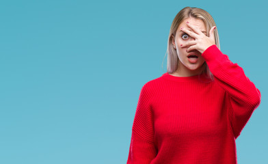 Young blonde woman wearing winter sweater over isolated background peeking in shock covering face and eyes with hand, looking through fingers with embarrassed expression.