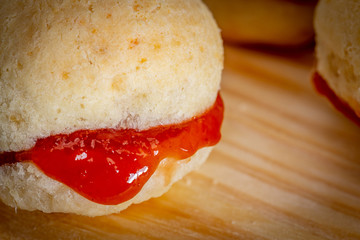 Brazilian homemade cheese bread AKA 'pao de queijo', stuffed with guava dessert, on a rustic background.