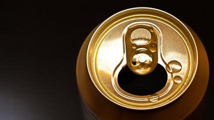 Obraz Plano detalle desde arriba de la boca de una dorada lata de aluminio sobre un fondo negro  con luz y enfoque selectivo. - fototapety do salonu