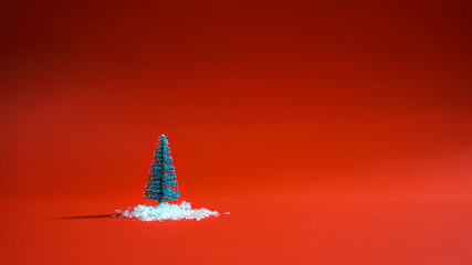 Top view snowy christmas tree with snow on the ground on red background. Minimal New Year concept. Flat lay