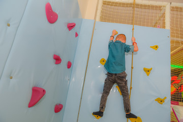 High dexterity pre school kid climbing up the wall created for climbing training inside of the kids playground and entertainment facility