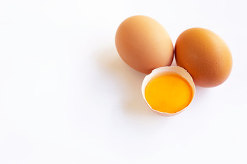 Chicken eggs with yolk on white background.