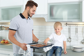 Young man treating his son with homemade oven baked cookies in kitchen