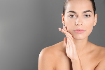 Portrait of beautiful young woman and space for text on grey background. Cosmetic surgery concept