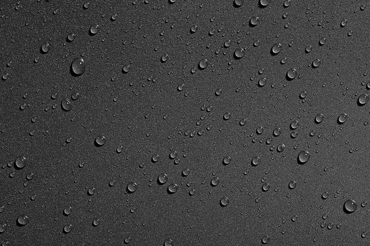 Water drops on black background, top view