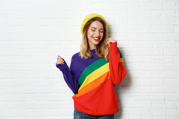Wall Mural - Beautiful young woman in warm sweater with hat near white brick wall