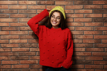 Beautiful young woman in warm sweater with hat near brick wall
