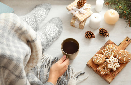 Woman relaxing with cup of hot winter drink at home, above view. Cozy season