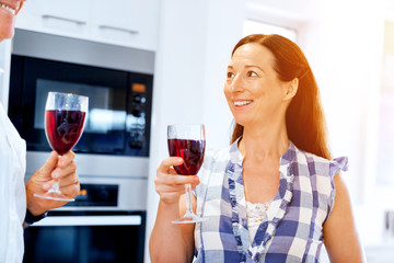 Senior woman with holding a glass of wine indoors