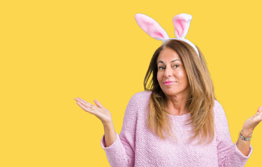 Middle age brunette woman wearing easter rabbit ears over isolated background clueless and confused expression with arms and hands raised. Doubt concept.