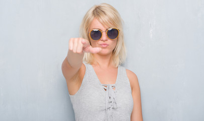 Adult caucasian woman over grunge grey wall wearing retro sunglasses pointing with finger to the camera and to you, hand sign, positive and confident gesture from the front
