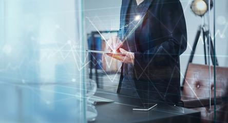 Businessman using digital tablet to analysis market sales growth thru virtual screen . Ecommerce marketing concept .