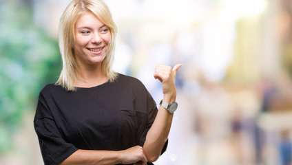 Young beautiful blonde woman over isolated background smiling with happy face looking and pointing to the side with thumb up.
