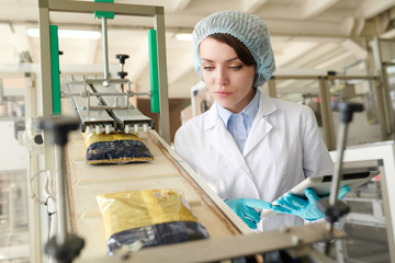 Portrait of young  woman controlling  packaging process at modern food factory and looking at macaroni bags sliding down conveyor belt, copy space