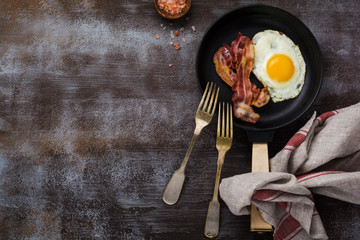 Aluminium Prints Egg Traditional English breakfast with fried eggs and bacon in cast iron pan on dark concrete background. Top view.