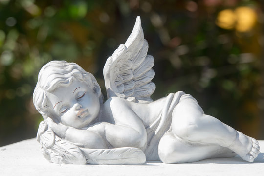 Sleeping of little cupid's ceramic doll on stone. Items for house, garden, and interior or exterior installed and cafe decoration.