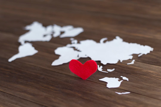 Red felt heart and world map cutted from white paper on the wooden background. Love concept. Close-up, soft focus, copy space, mock up, diagonal arrangement