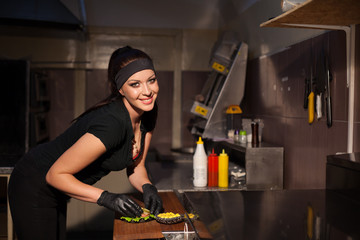 female chef preparing food in the kitchen of the restaurant Burger
