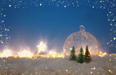 image of christmas trees inside glass ball over snowy wooden table.