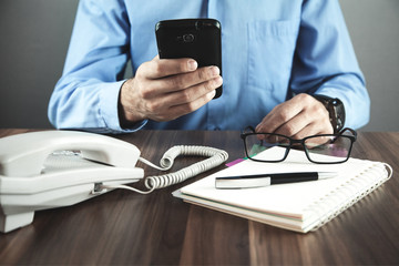Man using smartphone in his desk. Business concept