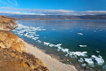Lake Baikal at spring morning. Top view of the coast of the Olkhon Island and the Small Sea Strait with white ice floes on blue water