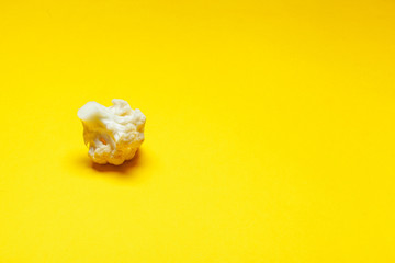 Cauliflower pieces on a bright yellow background