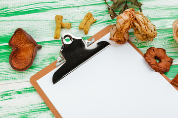 Clipboard with office supplies on green wooden table, flat lay