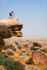 Photographer with tripod on the overhanging over plane rock cliff. Gobustan, Azerbaijan