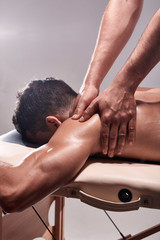 side view, two young man, 20-29 years old, sports physiotherapy indoors in studio, photo shoot. Physiotherapist massaging patient shoulder with his hands close-up.