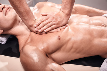 elevated view, two young man, 20-29 years old, sports physiotherapy indoors in studio, photo shoot. Masseur massaging athlete mans chest, muscular body, hands close-up.