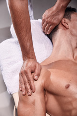 two young man, 20-29 years old, sports physiotherapy indoors in studio, photo shoot. Physiotherapist massaging mans back.