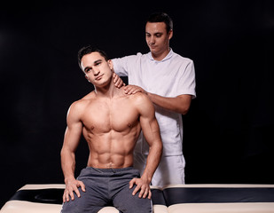 two young man, 20-29 years old, sports physiotherapy indoors in studio, photo shoot. Physiotherapist massaging muscular patient shoulder with his hands, while he is sitting on bed.