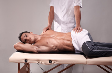 two young man, 20-29 years old, sports physiotherapy indoors in studio, photo shoot. Physiotherapist massaging muscular patient back with his hands.