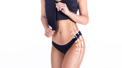 cropped image of a female body in black underwear, showing her waist and hips with arrows and lines. Slimming and fat removing concept
