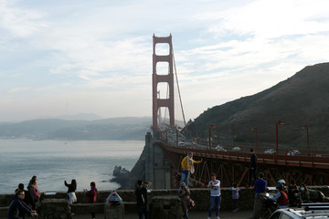 Tourists take photos in front of the Golden Gate Bridge in Sausalito