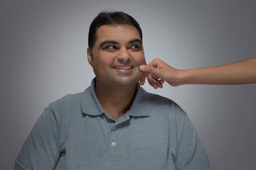 Portrait of smiling man with a hand pulling his cheek