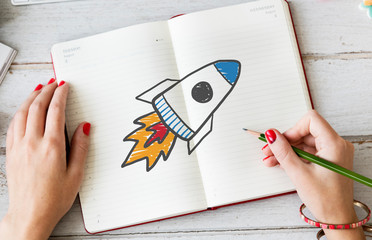Woman drawing a rocket launch on a notebook