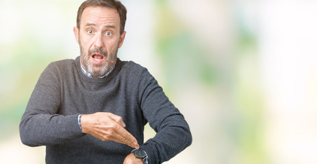 Handsome middle age senior man wearing a sweater over isolated background In hurry pointing to watch time, impatience, upset and angry for deadline delay