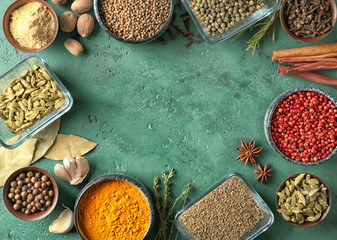 Frame made of different aromatic spices on color background