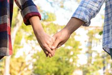 Young couple holding hands outdoors