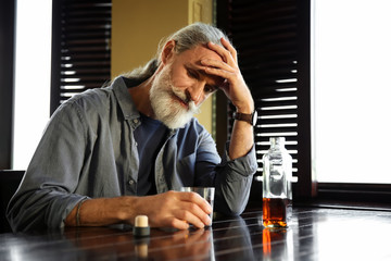 Depressed senior man drinking whiskey in pub